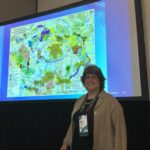 Alison in front of map projected on screen