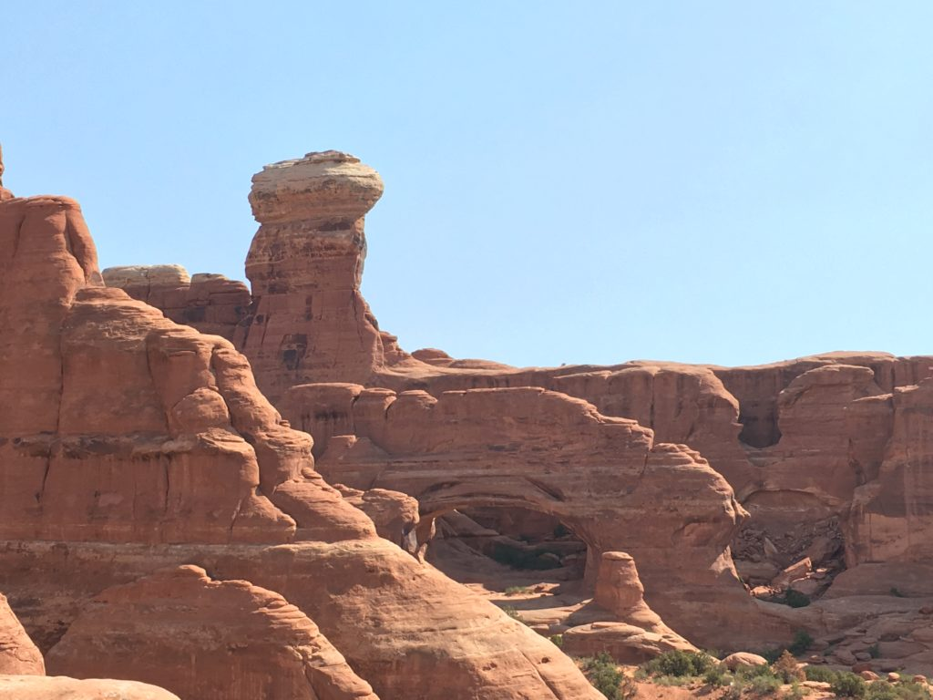 Sandstone arch in front of a sandstone tower.