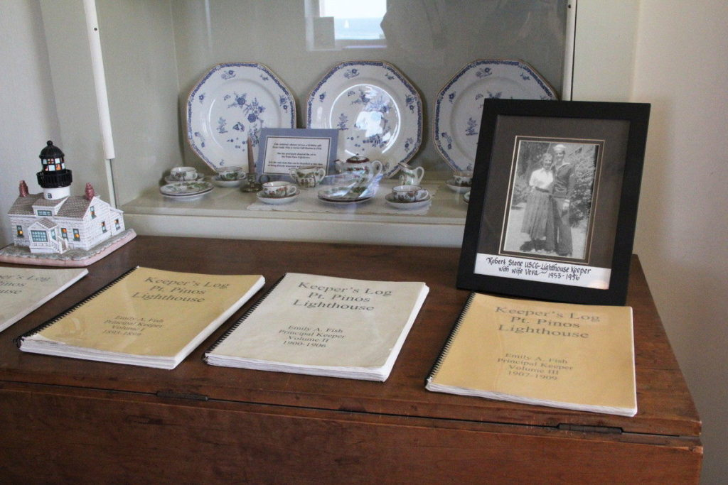 Display of lighthouse china, photo, and logbooks.