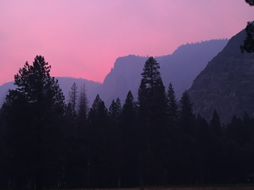 Bright pink sky behind purple mountains and dark trees