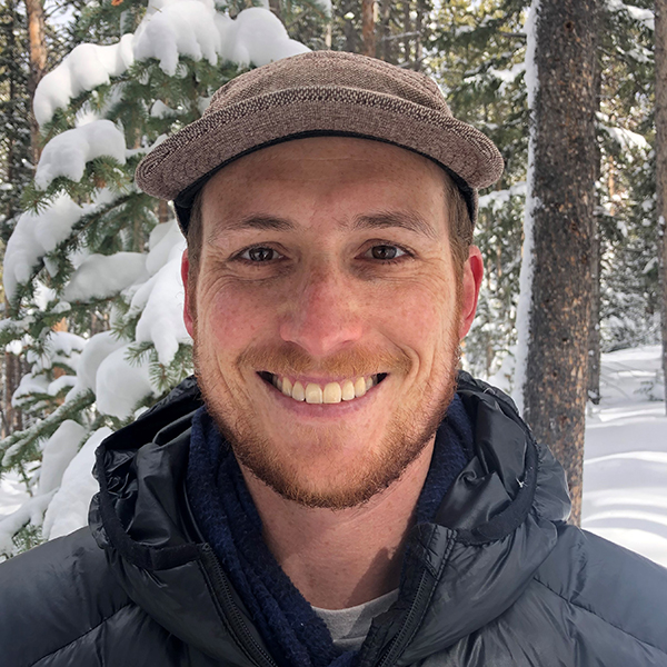 Aaron Sidder in winter jacket in front of snowy trees